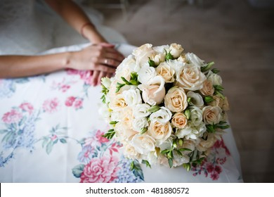 Wedding bouguet on table and bride's hands