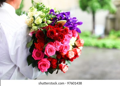 Wedding bouquet of beautiful colorful roses which are ready to present for bride and groom.