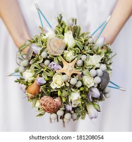 wedding bouquet of beige roses and leaves decorated with shells