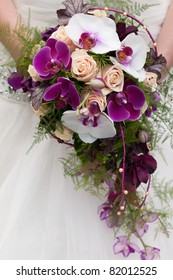 wedding bouquet of beige roses and purple orchids
