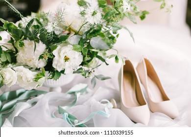 Wedding bouquet and bridal shoes on tissue