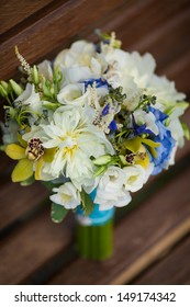 Wedding bouquet of bride. bridal flowers bouquet in wedding day. Wedding bouquet of yellow and white roses and blue fresia and orchids lying on wooden bench