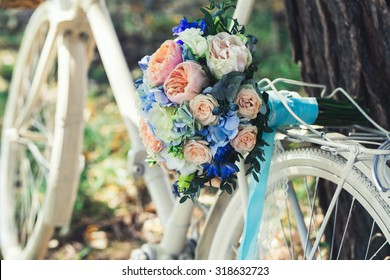 Wedding bouquet of bride - colorful flowers pink, white roses and blue freesia and hydrangea at wedding on nature