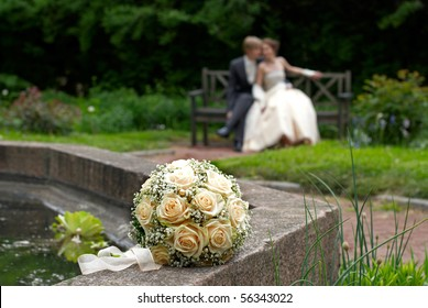 Wedding bouquet with bride and groom in background. Shallow DOF