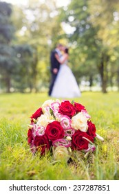wedding bouquet with bride and groom on background