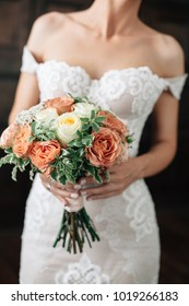 Wedding. Bouquet in bride hand. Bride in sexy wtite dress with red lips on dark background