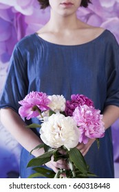Wedding bouquet of a bride from a peony in hand of bride