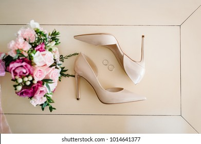 Wedding bouquet of the bride of pink flowers roses and greens, stylish elegant classic lacquered beige shoes and two silver wedding rings lying on pastel background. Close up. flat lay. top view.