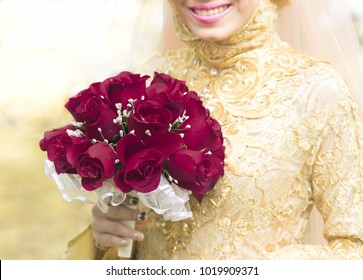 Wedding bouquet at bride's hand. Muslim bride holding a wedding bouquet in her hand, a bunch of red roses flower