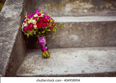 Wedding bouquet . The bride's bouquet. Bouquet of red and pink flowers, green leaf, with a ribbon of color Marsala standing on the steps