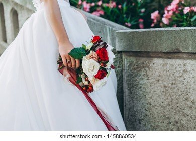 Wedding bouquet with bright flowers in bride's hand. Close up, no face seen.
