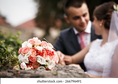 Wedding bouquet close up. Bride and groom in background. Shallow depth of field