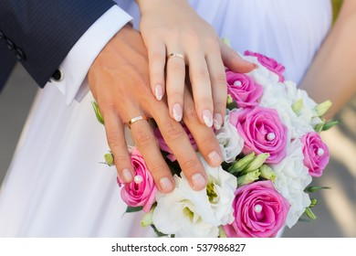 Wedding bouquet and couple hands with rings