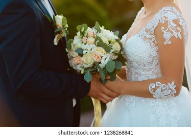 Wedding bouquet with delicate pink, beige, white flowers with green leaves in the hands of the brides in dress and costume, couple in love