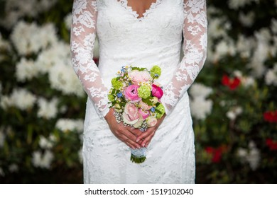 Wedding bouquet and dress with white roses as blurred background