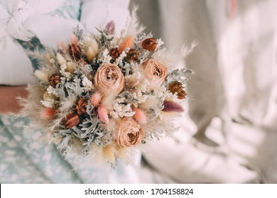 wedding bouquet of dried flowers in the hands of a florist - Shutterstock ID 1704158824