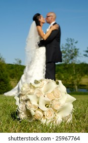 Wedding bouquet in focus and couple in blur