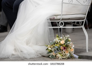 A wedding bouquet in front of a bench with a wedding dress