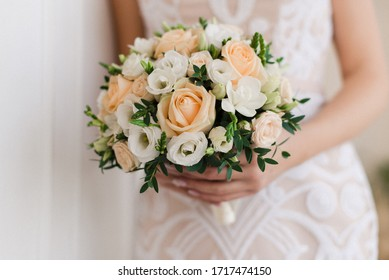 The wedding bouquet in the hands of the bride.
