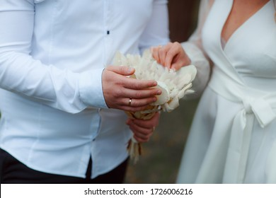 Wedding bouquet in the hands of the bride at the ceremony. Touching the hands of the bride and groom. Embrace of the newlyweds.
