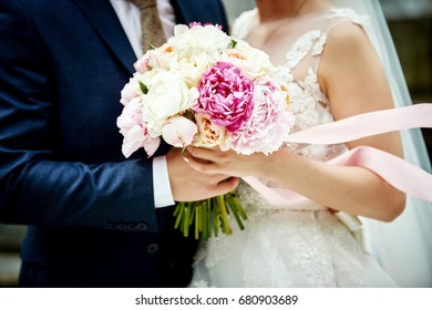 Wedding bouquet in the hands of the bride and groom of roses, peonies with a pink ribbon