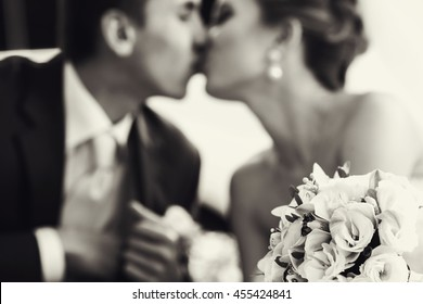 Wedding bouquet lies on the frontground of a black and white picture of kissing newlyweds