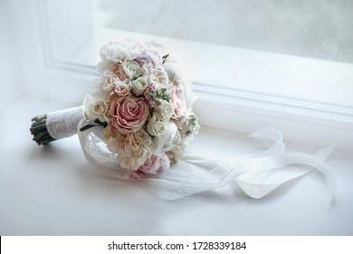 The wedding bouquet lies on the windowsill. Bouquet on a white background. Floral Designs on Instagram. Wedding trend of 2020. Wedding minimalism