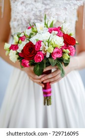 A wedding bouquet of light roses in the hands of the bride. Beige and pink flowers. Composition of gentle roses