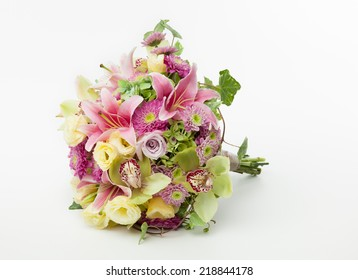 Wedding bouquet lying down on white background. Cymbidium Orchids, Roses, Chrysanthemum, Lily and Hydrangea flowers.