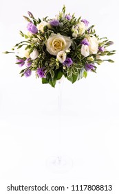 A wedding bouquet on a high glass vase