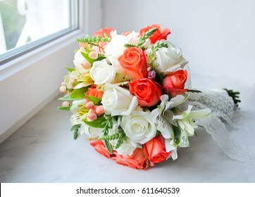 Wedding bouquet with orange and white roses on windowsill. Close up of bride bouquets with lace tape