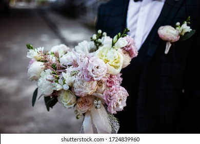 wedding bouquet of pastel roses at groom's hands