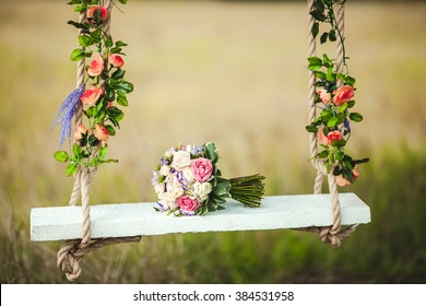 Wedding bouquet of peonies lying on a white bench swing decorated with fresh flowers.