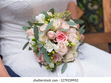 wedding bouquet of pink roses on the bride's lap in a white dress, flowers
