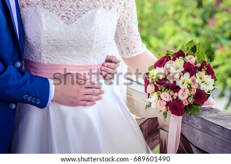 f6417e7c42e0 Wedding bouquet of red, pink and white roses and flowers in the hands of the