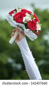 Wedding bouquet with red roses in hand of the bride