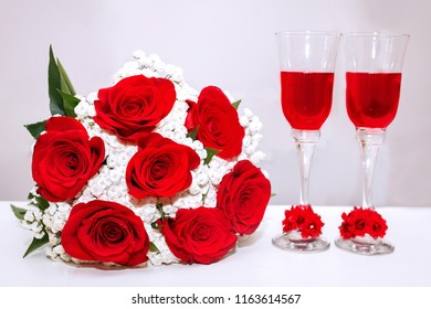 Wedding bouquet of red roses and two champagne glasses standing on the authentic . Background