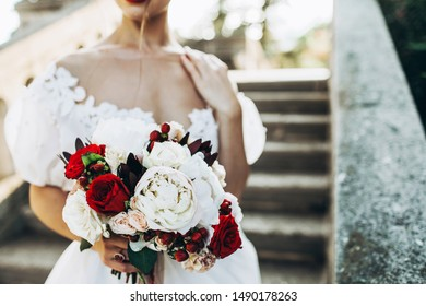 Wedding bouquet with red and white flowers in bride's hand. Close up, no face seen.