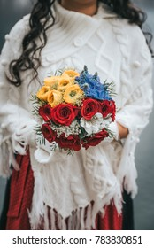 Wedding bouquet with red and yellow roses in bridals hand