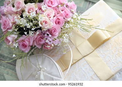 Wedding bouquet of roses, bag and elegant box with bow.