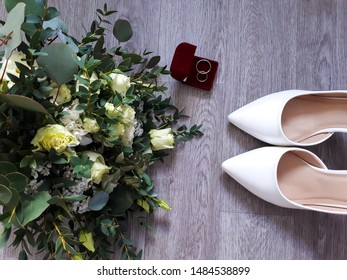 wedding bouquet with roses and eucalyptus, white wedding shoes and a red velvet box with rings for marriage registration
