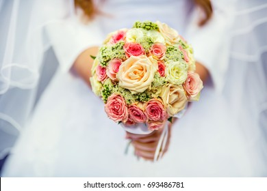 Wedding bouquet with roses in hands of bride.