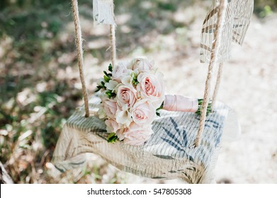 Wedding bouquet of roses lying on a white bench swing