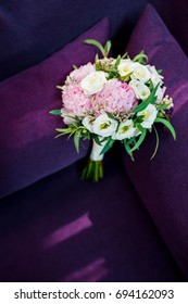 Wedding bouquet in the sunlight lies on the armchair