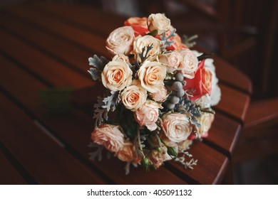 Wedding bouquet of various flowers on wooden table in cafe