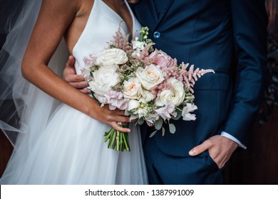 Wedding bouquet of white and pink roses and with newlywed couple