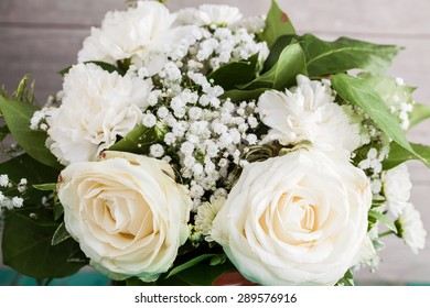 Wedding bouquet of white roses on a wooden table.