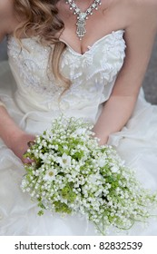 wedding bouquet of white small flowers lily-of-the-valley at girl's hand