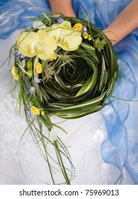 wedding bouquet of yellow orchid and green leaves