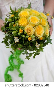 wedding bouquet of yellow roses at girl's hand